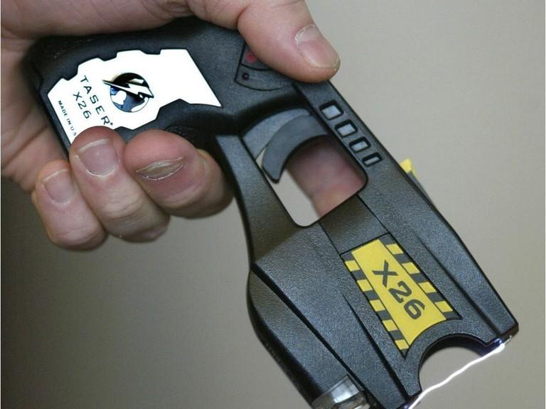 A police officer displays the Taser X26.