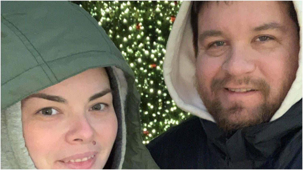 Joshua Paul and his wife, Ashley Gillin, in front of a Christmas tree. Paul recently collected Christmas trees in exchange for donations, which he turned over to Liverpool Street Elementary School's breakfast program.