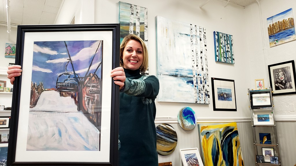 Connie Wheaton, artist, art teacher, and owner of the House of Art studio on Queen Street, holds up her painting Sunday afternoon of the Crabbe Mountain ski hill, which will be part of an online winter-themed art exhibition opening later this week.