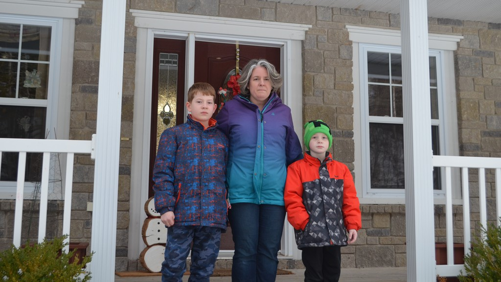 Leanne Perrin said she feels relieved knowing her two sons will remain in school even if the province puts the Fredericton region in the red phase of its COVID-19 recovery plan. She's pictured outside her home in Douglas, with her sons, Carter Perrin, left, and Spencer Perrin, right.