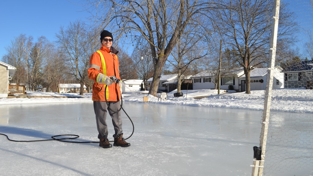 Earle Munn, a friend of David Green, helped build and continues to help maintain the backyard hockey rink they built outside Green's home in Skyline Acres. Munn is pictured flooding the ice to create a smooth surface.