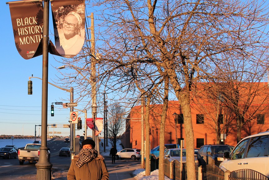 Fredericton's Mary Louise McCarthy, known for her work in uncovering New Brunswick's Black histories, stands under her banner in the city's downtown.
