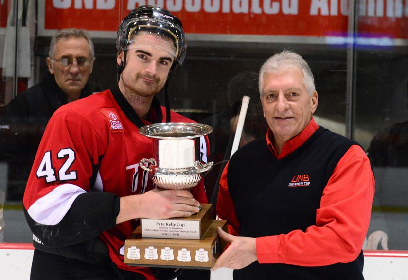 University of New Brunswick representative Dave Morell presents the 2014 Pete Kelly Cup to fifth-year defenceman Ben Shutron, who went on to work for Hockey Canada and has been hired by the NHL's Montreal Canadiens as amateur scout for Western Canada.