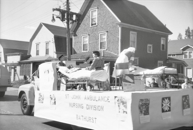 This Angus Branch photo from the Bathurst Heritage Museum features a St. John Ambulance parade float along King Avenue in Bathurst, likely from the early 1960's.