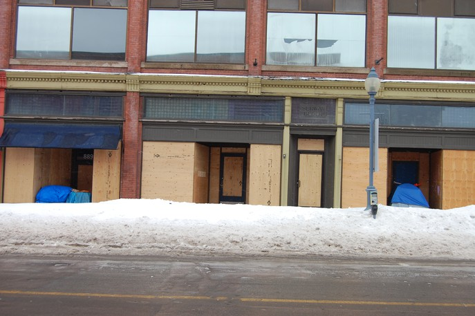 A tent and shopping carts covered by tarps are tucked in doorways outside the boarded-up Subway Block in downtown Moncton on Feb. 17, 2021.