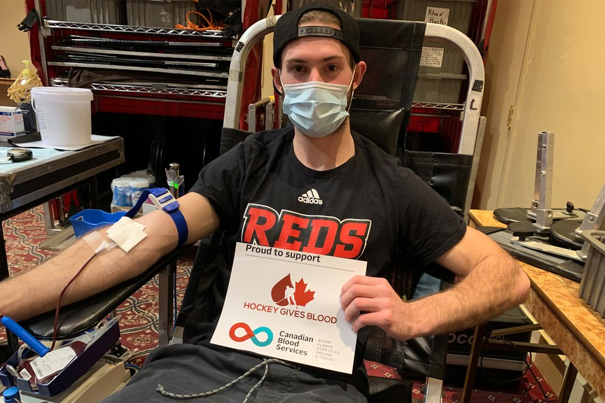 Austen Keating, a first-year member of the UNB men's hockey team, donates blood on Wednesday evening, part of the Reds first experience with the Hockey Gives Blood initiative.