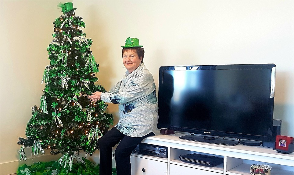 Lorraine Arsenault of Fredericton embraces her Christmas tree. Arsenault said she decided to leave it up after Christmas because it helped lift her spirits during the pandemic. She decorated it for Valentine's Day and now has it decked out for St. Patrick's Day.