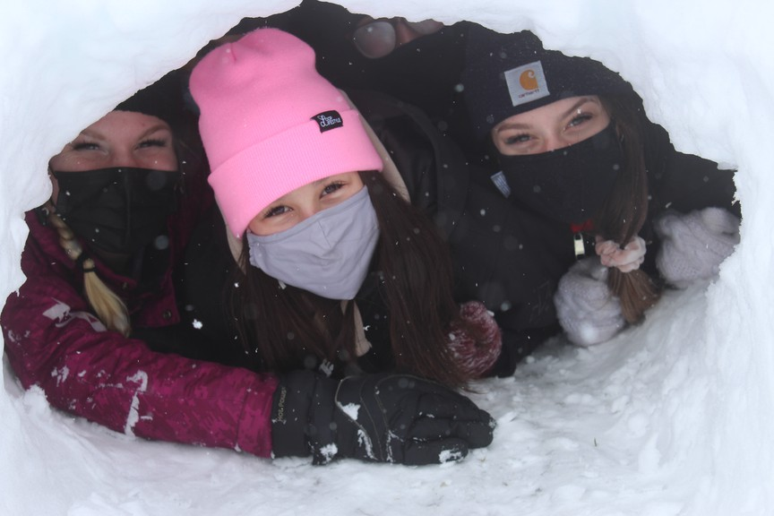 Tori Lane, left, Breanna Lee and Olivia Kenny, Grade 12 students from Bathurst High School's outdoor pursuits class, pose for a photo from inside one of the quinzees they helped build at the high school.