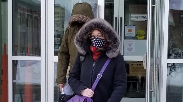 Kim Stanley Wong, left, leaves the Saint John Law Courts, his face obscured by a hood, mask and his fully zipped parka on Tuesday afternoon escorted by his lawyer Maria Powell after being sentenced for taking a secret recording of a female employee getting changed at the Sussex Tim Hortons where he was manager in 2019.
