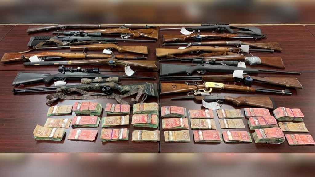 The RCMP says officers seized these guns and this cash at a raid at a Tobique First Nation home Friday evening.