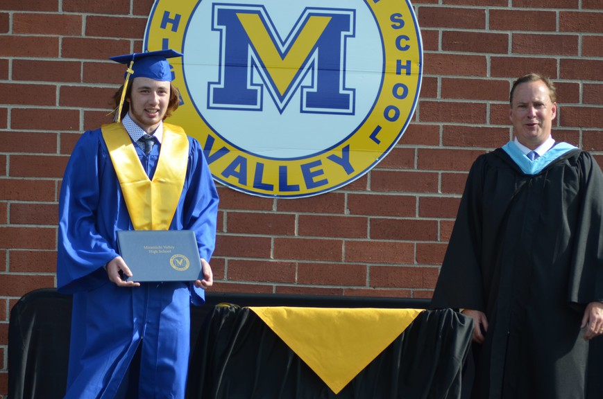 Ethan Arbeau, left, a 2020 Miramichi Valley High School graduate, accepts his diploma from school principal Shawn Wood during a drive-thru grad ceremony held due to concerns about COVID-19. Anglophone North School District superintendent Mark Donovan says traditional grad ceremonies could return this year, pending COVID-19 protocols.