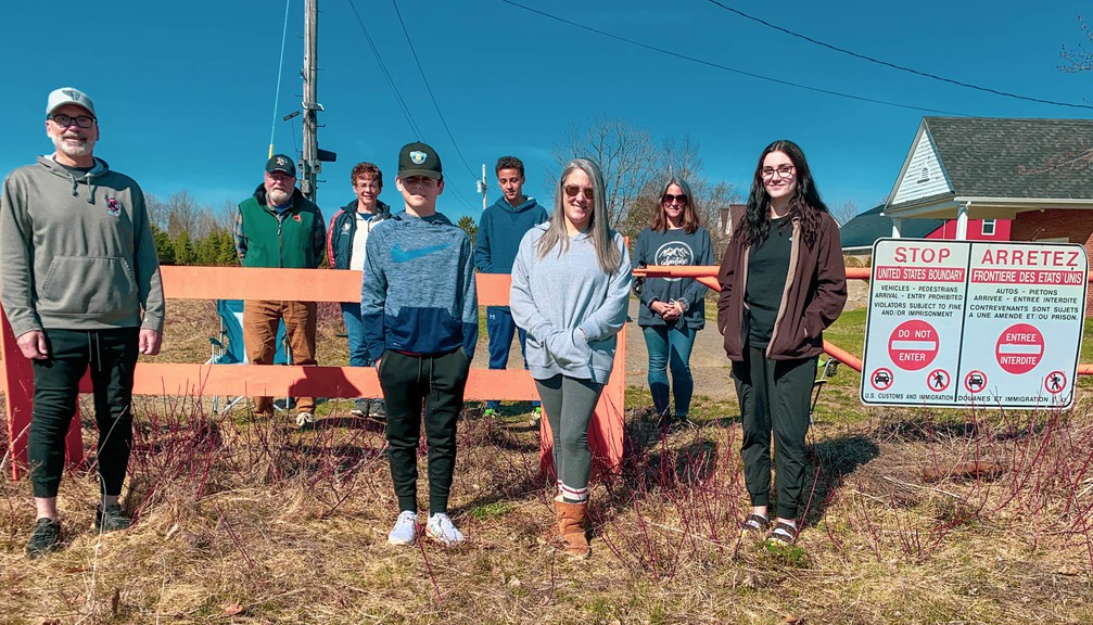 Cortney Rector visits with her American family at an old border crossing near Woodstock. In front, from left, are Jeff Rector, Jackson Rector, Cortney Rector and Maya Rector. In back on the Maine side of the border are Cortney's parents Ken and Clare Arndt, nephew Kai Taylor and twin sister Kirsten Arndt.