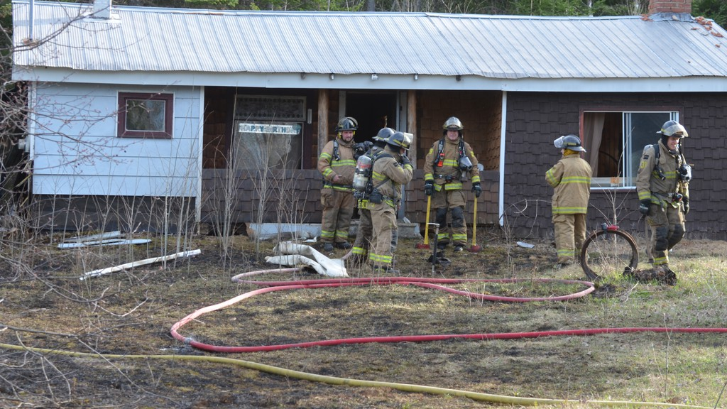 Hartland firefighters look over the scene of a grass and bungalow fire in Mainstream on Wednesday evening.