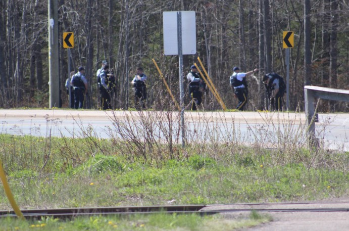 RCMP members search for evidence near the Millennium Boulevard entrance to Centennial Park on May 13.