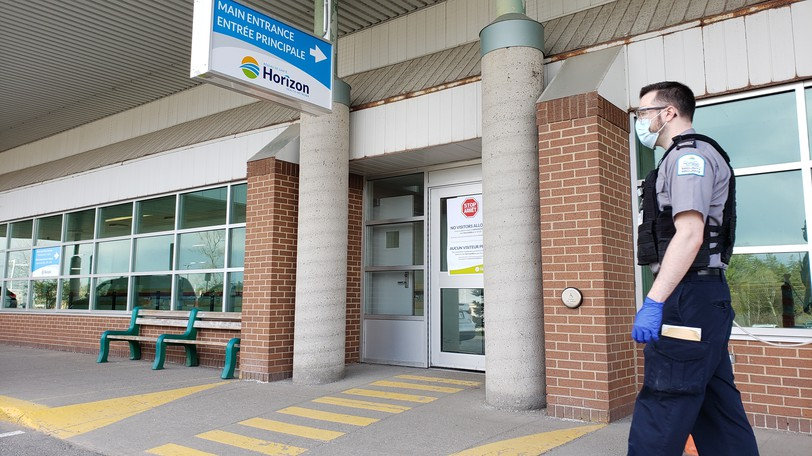 In this file photo, a Horizon Health Network security guard keeps an eye on the doors of the Dr. Everett Chalmers Hospital in Fredericton.