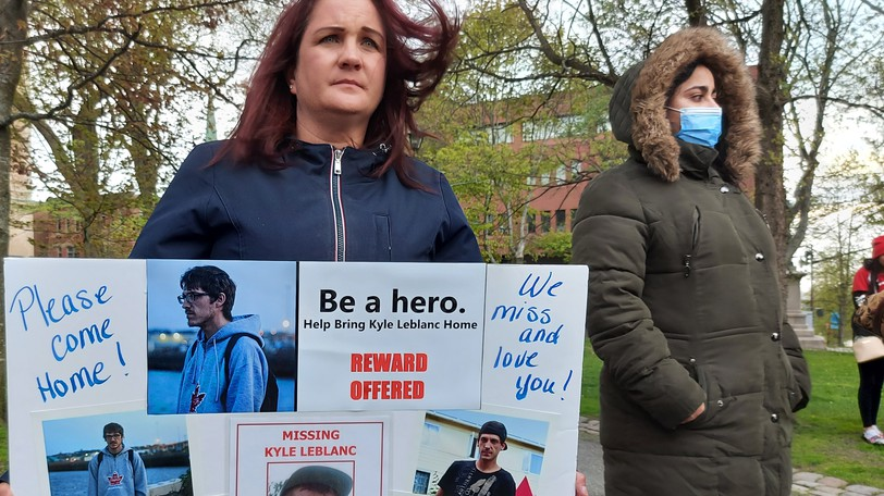Erin LeBlanc, Kyle LeBlanc's stepmother, holds up a sign dedicated to him at a vigil to mark National Missing Children's Day. The 30-year-old Saint John man has been missing since December.