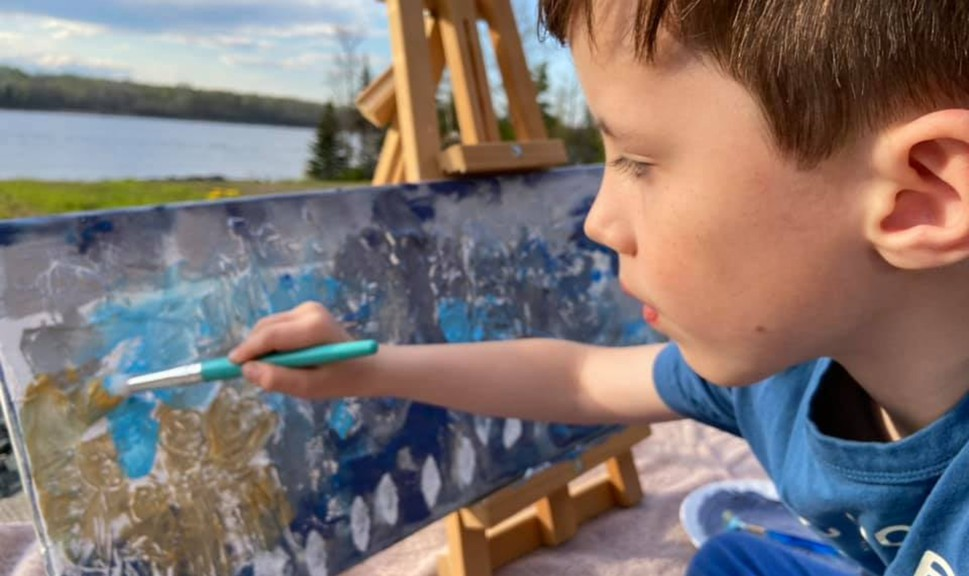 Seven-year-old Chance McCormack working on a painting he's raffling off to raise money for a bursary in memory of his cousin Denver Jardine, one of three teens killed in a car accident in Blackville last September.