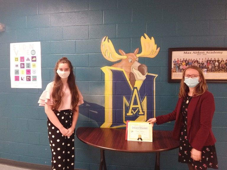 Reese Vickers, left, a Grade 7 student at Max Aitken Academy, accepts her grand prize for winning the Miramichi Literacy Council's recent poetry contest from Nadine Pesch, community engagement co-ordinator for the literacy council.