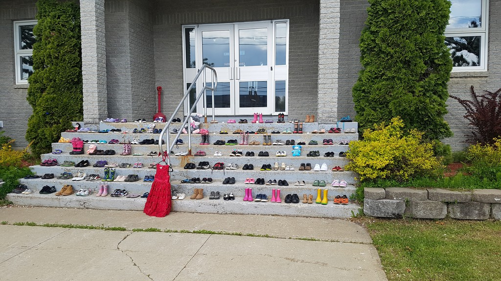 Shoes placed as a memorial at  Eel River Bar (Ugpi'Ganjig) First Nation  to the 251 Indigenous children whose remains were found buried on the grounds of a former residential school in British Columbia. Columnist Bill Clarke ponders this week how such a thing could have happened.