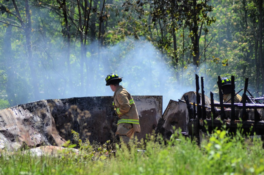 Miramichi firefighters sift through debris Wednesday at a fire that destroyed two abandoned mobile homes on Maple Grove Court, in the former town of Chatham.