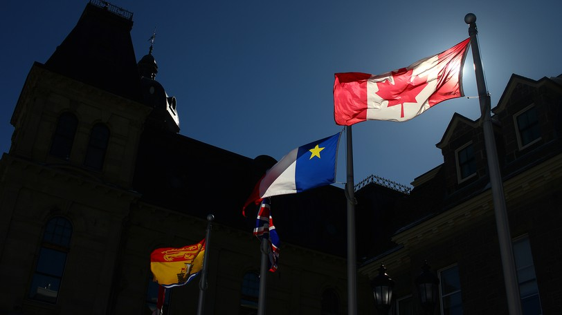 The Canada flag flies among others at the Legislative Assembly.