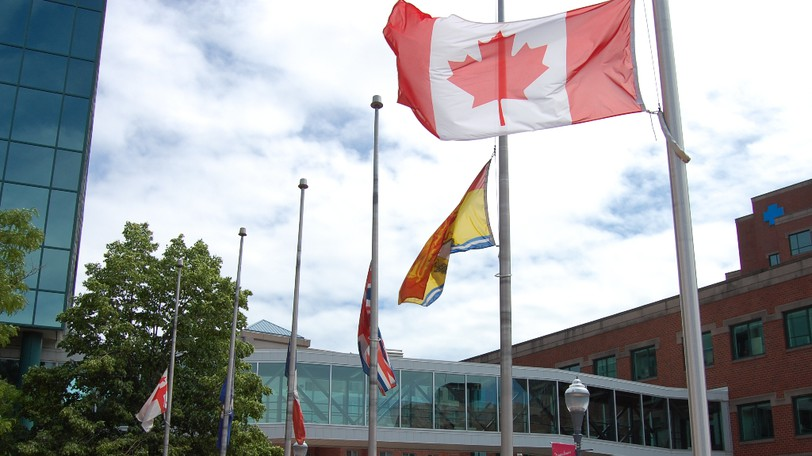 Flags fly at half-mast outside Moncton city hall in June following the discovery of hundreds of unmarked graves outside residential schools.