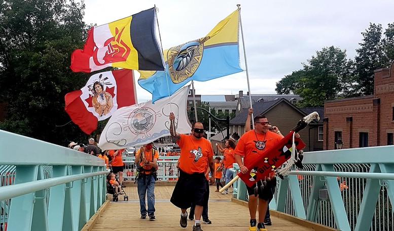 Indigenous flags led the way during a Canada Day healing walk in Fredericton that paid homage to Indigenous children discovered in unmarked graves at or near former residential schools across the country.
