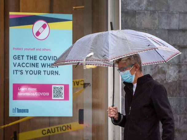 A pedestrian wearing a mask walks past a poster encouraging Torontonians to get the COVID-19 vaccine when it is their turn, at the corner of Church and Queen Streets, on Thursday, July 8, 2021.