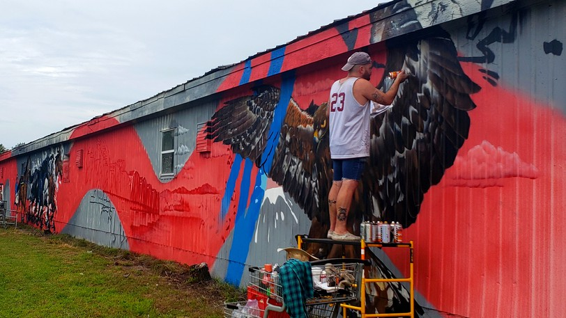 Donny Fraser-Fong, an artist with Halifax-based mural design company Trackside Studios, paints an eagle on the side of a horse barn at the New Brunswick Exhibition Wednesday morning, as part of a new 200-foot-long mural.