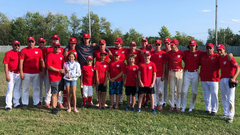 Quinn Jones and the 18U Woodstock Shiretowners present 11U Shiretowners coach David McElwain with a donation of $250 to go toward the team's upcoming trip to Newfoundland to play in The Atlantic Tournament. The team is trying to raise $30,000 to cover travel expenses.