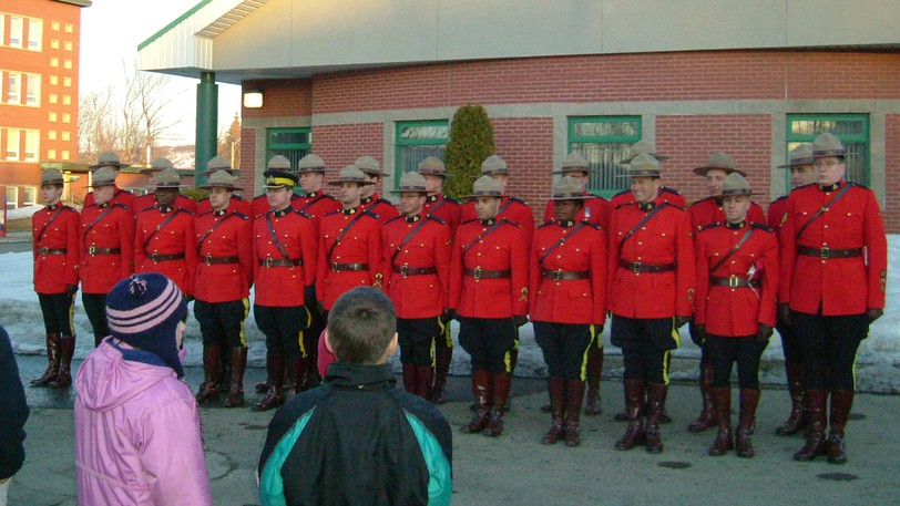 RCMP officers in red serge dress uniform outside the Campbellton detachment are shown in this file photo. RCMP members have ratified a new collective agreement, and while not all details are in, it is certain to mean much higher costs those municipalities which use the the force.