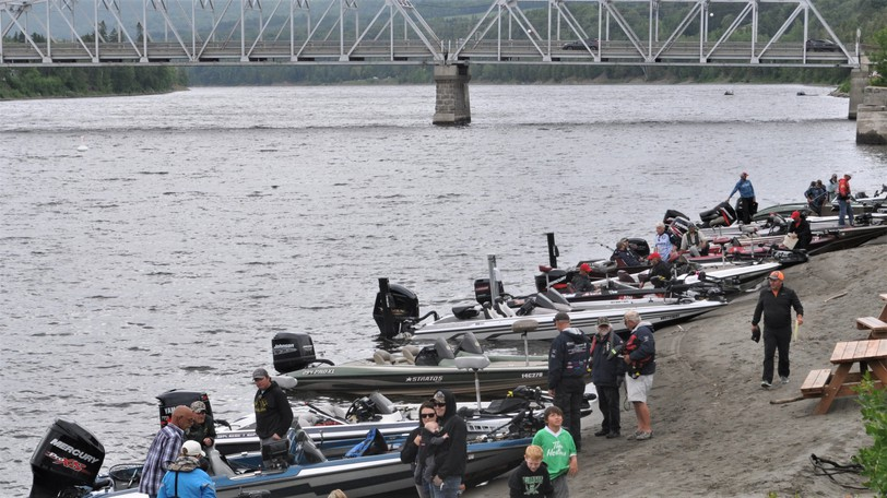 Bass fishing boats line the shore of the St. John River at Perth-Andover at a tournament in 2019. Fishers took to the water on Aug. 14 this year in search of the biggest smallmouth bass.