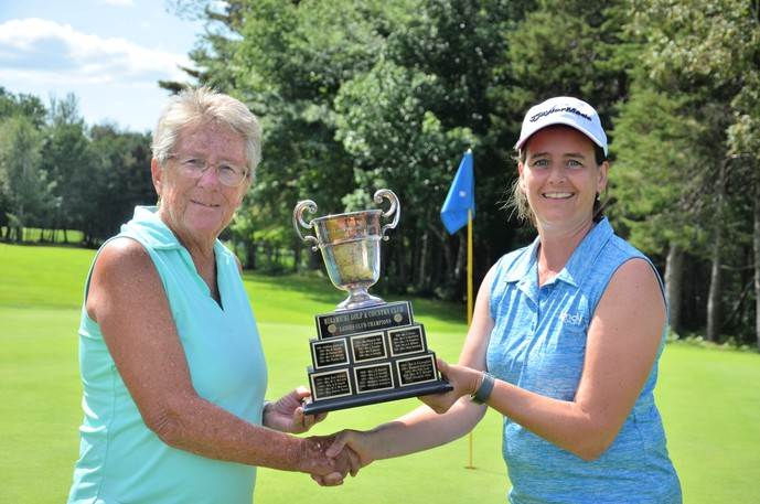 Heather Wood, left, accepts the Miramichi Golf and Country Club ladies' club championship trophy Sunday from ladies' club captain Cheryl Carroll.