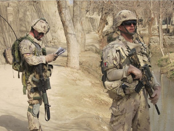 Capt. Eric Bouchard, left, checks his map while Cpl. Eric Gauthier stands guard during a foot patrol by Canadian soldiers in a village in central Panjwaii, Afghanistan on Feb. 19, 2011.