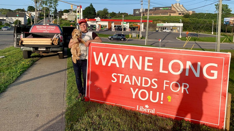 Saint John-Rothesay's Liberal candidate Wayne Long stands next to one of his election signs that bears a Canadian Union of Public Employees sticker.