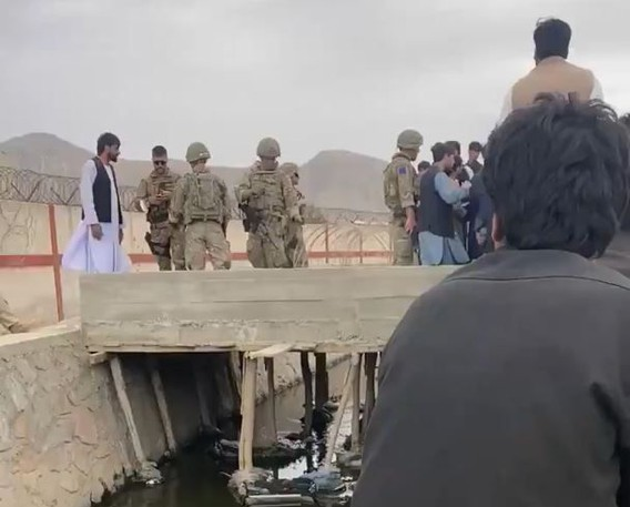American and Afghani troops speak to an evacuee at the north gate of Hamid Karzai International Airport in Kabul, Afghanistan on Saturday, Aug. 21 2021.
