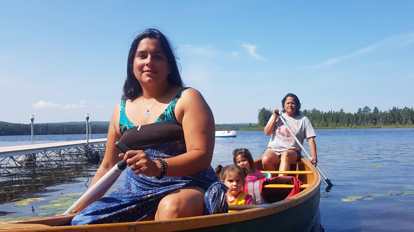 Brandy Stanovich with her daughters two-year-old Aselis Paul, four-year-old Pakwahson Paul and Connecting with the Land board member Andrea Polchies on Miramichi Lake on Sunday.