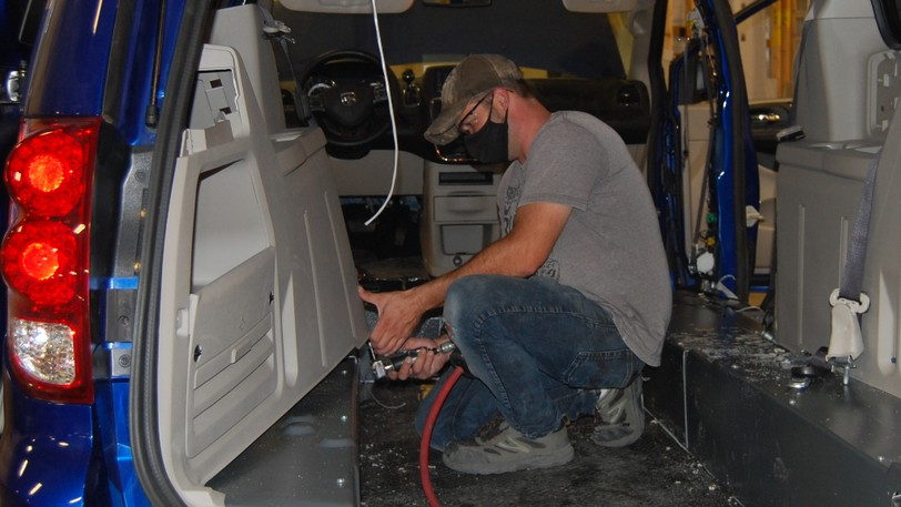 Rodney Nicholson reassembles the interior of a van on Tuesday following the installation of a wheelchair ramp at Malley Industries in Dieppe, where six business associations outlined their demands for the next federal government.