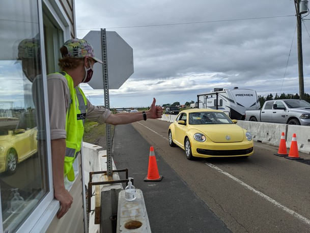 Nova Scotia border official Ben Capon gives a thumbs up to a car crossing the border from New Brunswick Tuesday afternoon.