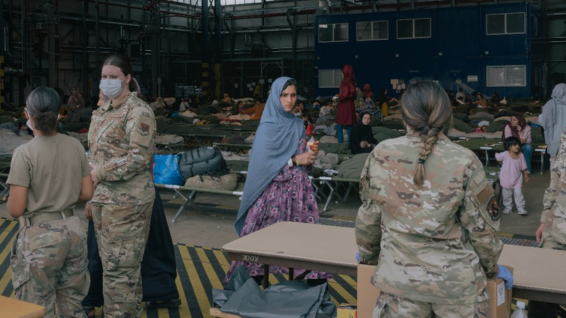 An Afghan evacuee waits for diapers in a hangar at Ramstein Air Base in Germany on Tuesday, Aug. 24, 2021.