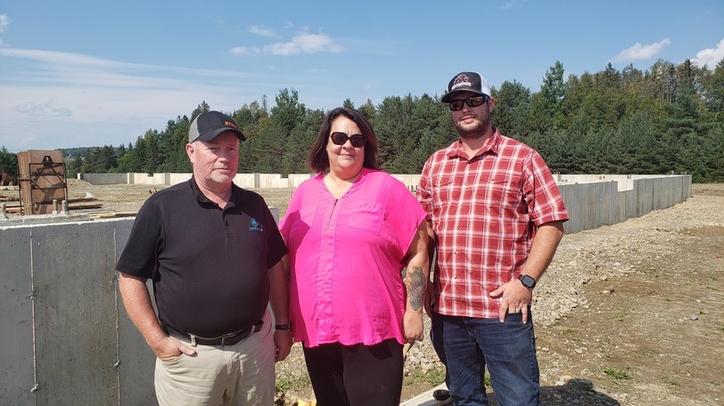 Florenceville Ag owners Jeff Sherwood, Wendy Sherwood, and Andrew Kennedy stand in front of the building site for their new store. The original building burned down in March.
