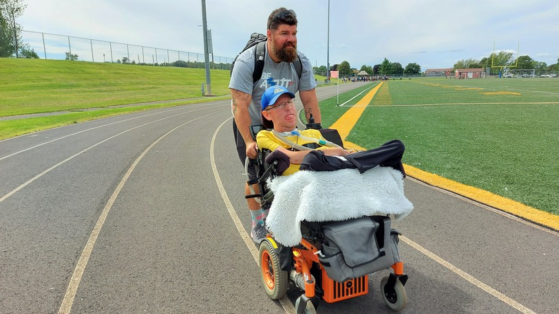 Derrick May pushes John Wood around the track at LeRoy Washburn Field in Oromocto on Friday afternoon for the final lap of The Summerville 500 - a 500-mile walk for the John Wood Foundation.