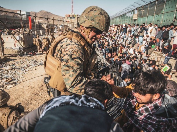 A U.S. Marine assists at an Evacuation Control Check Point during an evacuation at Hamid Karzai International Airport, Kabul, Afghanistan, on Aug. 26.