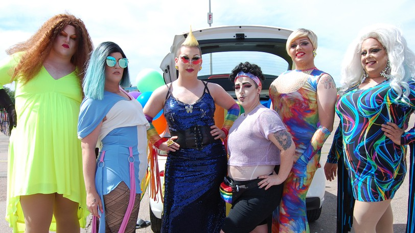 From left, drag performers Penny Codiac, Porcelain Barbie, Sabrina Knox, Justin Toodeep, Nova Gyna and Equi Knoxx are pictured at River of Pride's 'stationary parade' outside the Moncton Coliseum on Saturday.