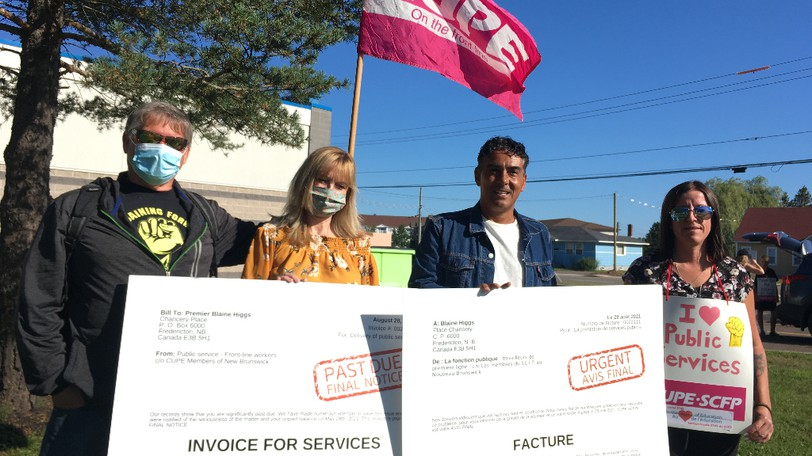 """Holding an """"invoice for services"""" addressed to Premier Blaine Higgs outside New Brunswick Community College in Moncton on Saturday are, from left, Jerry Knowles, president of the Canadian Union of Public Employees Local 720; Kim Copp, secretary treasurer for CUPE New Brunswick; Marcos Salib, CUPE national representative, Moncton area office; and Melissa Brown, president of the Moncton and District Labour Council."""