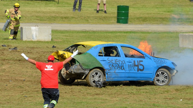 Firefighters race to put out flames on a car during the Richard Sharpe Memorial Demolition Derby and Tuff Trucks event on Saturday.