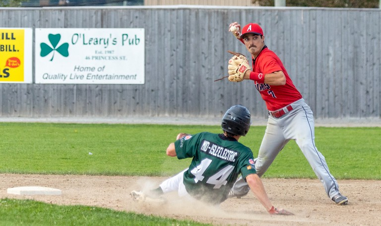Saint John Alpines shortstop Adam Clark, right, steps past Logan MacDougall (44) of the Charlottetown Islanders and delivers a throw to first base to complete a double play during the opening game of the New Brunswick Senior Baseball League semifinal series Saturday in Saint John.