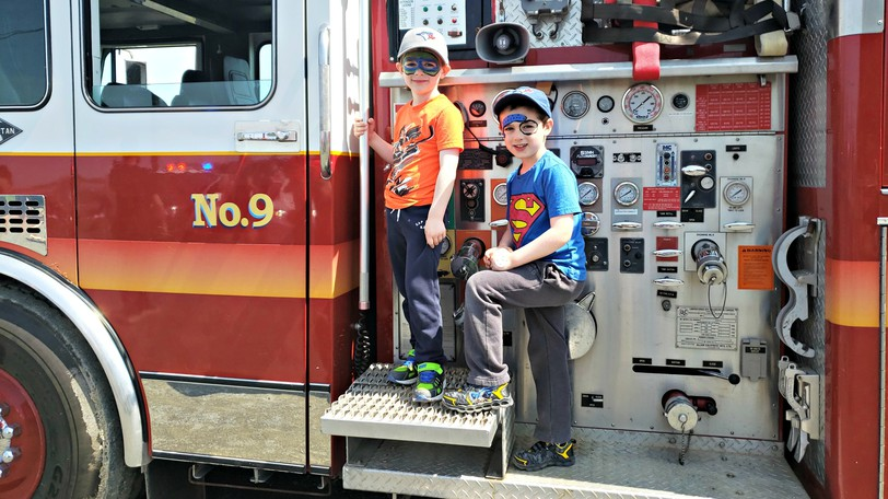 Logan and Gavin Schriver pose for a photo while standing on a fire truck from the Hartland Fire Department during a Touch A Truck event in Woodstock in a file photo. People will get a chance to interact with first responders and check out their equipment at the Woodstock Police Force Public Safety Event on Sept. 11.