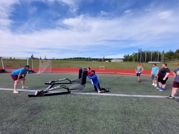 Defensive line coach Jerrad Fawcett, with the University of New Brunswick Saint John Seawolves, works with new try-out football players at the Canada Games Stadium.