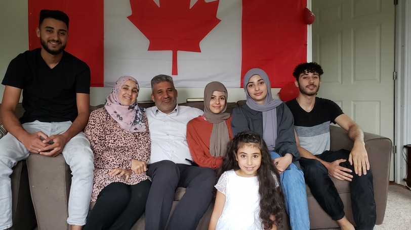 This Syrian family has settled happily into Fredericton. They officially became Canadian citizens, sworn in last week. The family includes, from left, Mohammed Albrdan, 21, his mother Manal Hrdeen, father Qassim Albrdan, sister Doaa, 15, sister, Alaa, 16, brother Abdulla, 19 and in the front row, eight-year-old sister Haya.